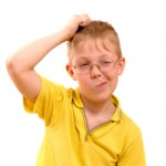 Boy scratches his head in puzzlement or confusion