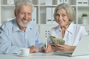 old couple holding cash