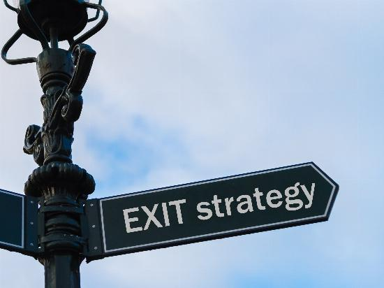 "A streetlight with a directional arrow reading, ""Exit Strategy."""