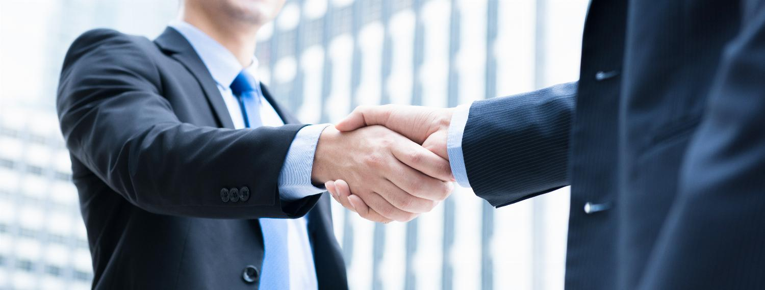 Two businessmen shake hands outside on a sunny day.